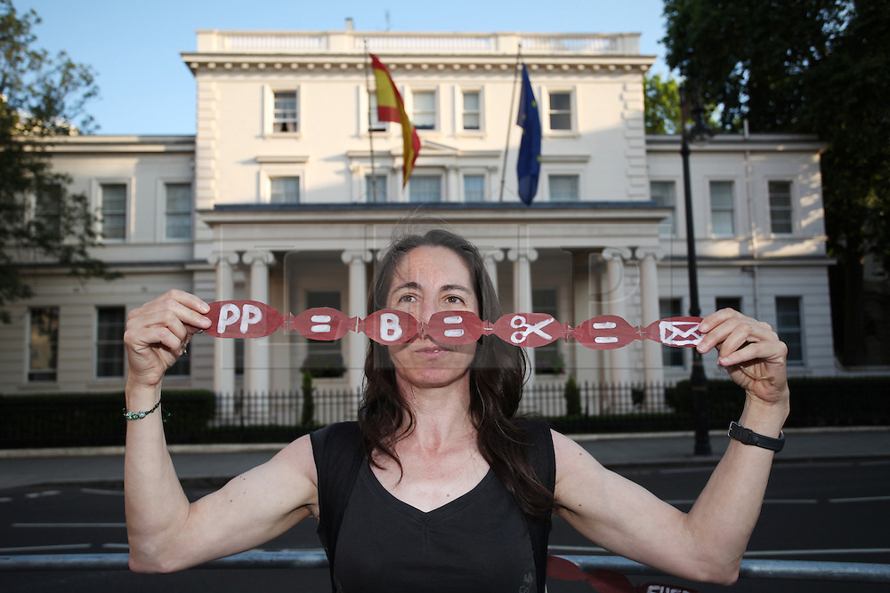 """© Licensed to London News Pictures . 18/07/2013 . London, UK. A Spanish protester holds a string of chorizos - spicy sausages- outside the Spanish Embassy in Belgrave Square, London, as a symbol of the Government's corruption. The word chorizo means """"thief"""" in Spanish slang. Federico Trillo-Figueroa, the Spanish ambassador to Britain, has been recently accused of receiving €128,000 from a secret slush fund while serving as Defence Minister for the centre-right Popular Party (PP) Government of José Maria Aznar, former Prime Minister. The accusations were made by former treasurer of the Popular Party Luis Bárcenas, who is currently awaiting a trial on fraud charges.Photo credit : /LNP"""