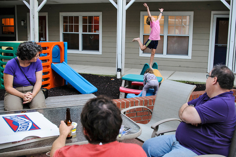 photo by Matt Roth..Takoma Village Cohousing residents Paul Schwartz, right, Betsy, left, and Eric Mendolsohn, middle, watch Betsy and Eric's children Imogen, 4, and Franklin, 10, play in the Washington, D.C. condo complex's tot lot Monday, September 24, 2012.
