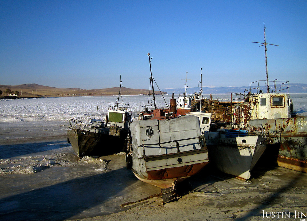 Boats lay idle on Olkhon Island on frozen Lake Baikal in Siberia, Russia. .They are a group of five people: Justin Jin (Chinese-British), Heleen van Geest (Dutch), Nastya and Misha Martynov (Russian) and their Russian guide Arkady. .They pulled their sledges 80 km across the world's deepest lake, taking a break on Olkhon, the world's forth-largest lake-bound island. They slept two nights on the ice in -15c. .Baikal, the world's largest lake by volume, contains one-fifth of the earth's fresh water and plunges to a depth of 1,637 metres..The lake is frozen from November to April, allowing people to cross by cars and lorries.