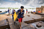 13 JUNE 2013 - YANGON, MYANMAR:  Porters pull ice chests of fresh fish off the jetty in the Annawa Fish Market. The Annawa Fish Market in Yangon is one of the largest fish markets in Myanmar. It serves as both a wholesale and retail market and serves both exporters and domestic customers. With thousands of miles of riverine waterways and ocean coastline Myanmar has a large seafood and fishing industry.   PHOTO BY JACK KURTZ