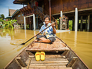 30 SEPTEMBER 2016 - SAI NOI, AYUTTHAYA, THAILAND: An 80 year old woman paddles her canoe through Sai Noi, a flooded village on the Chao Phraya River. The Chao Phraya River, the largest river that runs through central Thailand, has hit flood stage in several areas in Ayutthaya and Ang Thong provinces. Villages along the river are flooded and farms are losing their crops due to the flood. This is the same area that was devastated by floods in 2011, but the floods this year are not expected to be as severe. The floods are being fed by water released from upstream dams. The water is being released to make room for heavy rains expected in October.      PHOTO BY JACK KURTZ