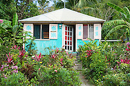 A traditional wooden chattel house surrounded by a garden of colourful tropical<br />