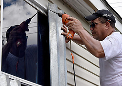 September 7, 2017 - Davie, Florida, U.S.- EDWIN OLIVANCIA helps his neighbors put up shutters onto their trailers at the SAGA Estates Mobile Home Park Thursday before Hurricane Irma possibly hits South Florida.  There is a mandatory evacuation for all mobile home residents.  (Credit Image: © Taimy Alvarez/Sun-Sentinel via ZUMA Wire)
