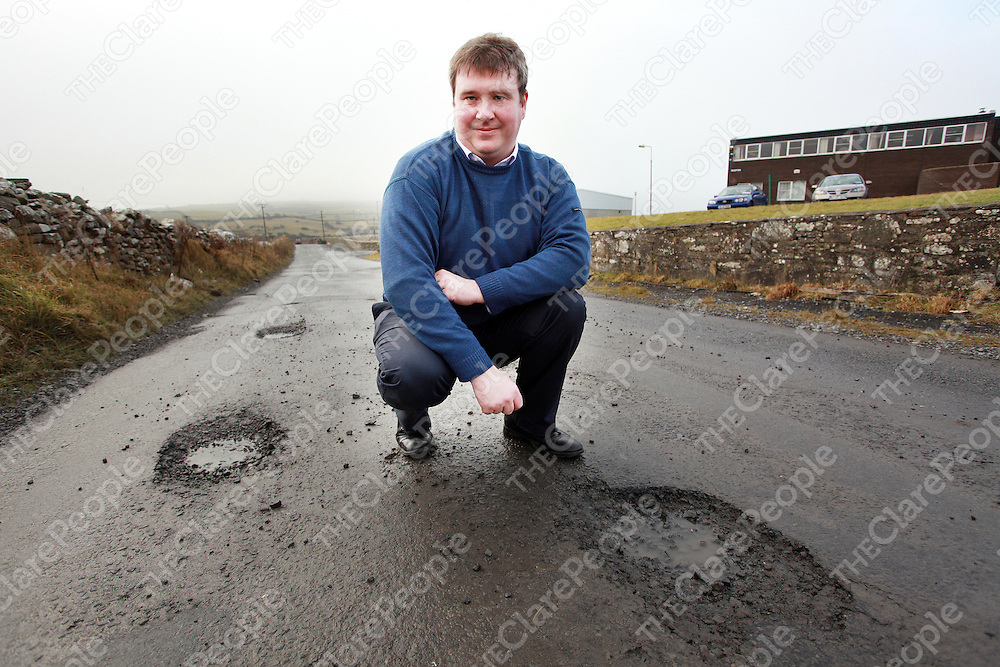 North Clare councillor Martin Conway examining the state of the roads after huge pot holes developed after weeks of freezing temperatures.<br /> Photograph by Yvonne Vaughan