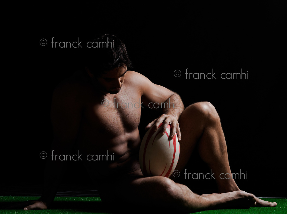 one caucasian sexy naked  man full length sitting holding rugby ball on studio black background