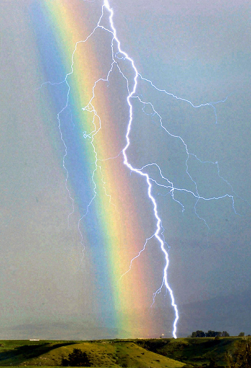 A lightning bolt strikes through a rainbow during an afternoon storm near the Big Horn mountians Friday.