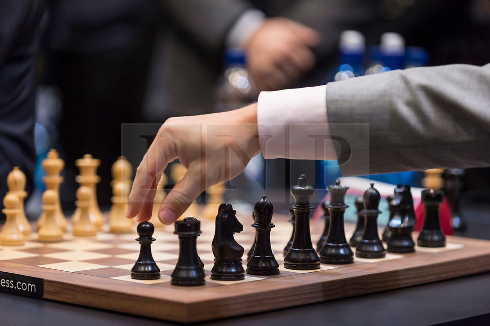 © Licensed to London News Pictures. 26/11/2018. LONDON, UK.  London, UK.  26 November 2018.  Magnus Carlsen of Norway plays a moves against Fabiano Caruana of the United States in the 12th game of the World Chess Championship taking place at The College in Holborn.  The 12 game match is currently tied after 11 draws.  Photo credit: Stephen Chung/LNP