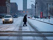 10 JANUARY 2020 - DES MOINES, IOWA: A man crosses Mulberry Street in downtown Des Moines during a snowstorm Friday. The first significant snow in two months blanketed Des Moines Friday evening. Meteorologists are predicting up to six inches of snow overnight and have issued a winter storm warning for southern and central Iowa. Most schools in the affected area closed early and cancelled afternoon events. Some presidential candidates, campaigning ahead of the Iowa Caucuses, cancelled their events.     PHOTO BY JACK KURTZ