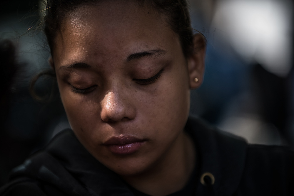 CARACAS, VENEZUELA - MAY 5, 2015: A young wife mourns the death of her husband, while waiting outside the city morgue to pick up his corpse. Her husband, who worked as a motorcycle taxi driver, was shot to death by thugs who stole his motorcycle.   Caracas, the capital of Venezuela has one of the highest homicide rates in the entire world.  PHOTO: Meridith Kohut for Buzzfeed News