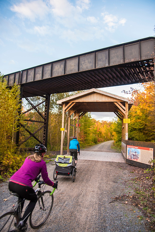 Family biking along the Iron Ore Heritage Trail, a multiuse recreation trail connecting communities in Marquette County on Michigan's Upper Peninsula. The route passes beneath an active rail line carrying iron ore pellets from mines to shipping docks on Lake Superior.