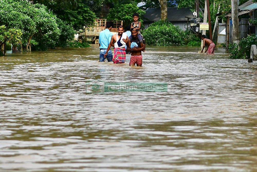 June 15, 2018 - Agartala, Tripura, India - Men are seen walking through the flooded water..Indian villagers  are leaving their houses with their children as the flood water has enter their houses after a heavy downpour in Baldakhal village, on the outskirts of Agartala the capital of northeastern state of Tripura, India. National Disaster Response Force (NDRF) personnel are rescuing people, children from different places and bringing them in safe places. (Credit Image: © Abhisek Saha/SOPA Images via ZUMA Wire)