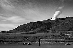 Man using his mobile phone in the geothermal hotspring area at Krysuvik, Iceland - Maður að lesa í farsíma við Krýsuvík