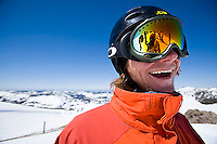 Young man smiling at camera while snowboarding at Kirkwood resort near Lake Tahoe, CA.