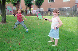 Brother and sister playing with a bat and ball game,
