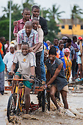 Dar es Salaam, Tanzania -   2015-05-07  - Pedestrians make their way across flooded Morogoro Road on a tricycle in Dar es Salaam, Tanzania on May 7, 2015. The Tanzania Meteorological Agency warned of 50mm of rainfall on May 6 and 7 due to a low pressure system developing in the Indian Ocean.  Photo by Daniel Hayduk