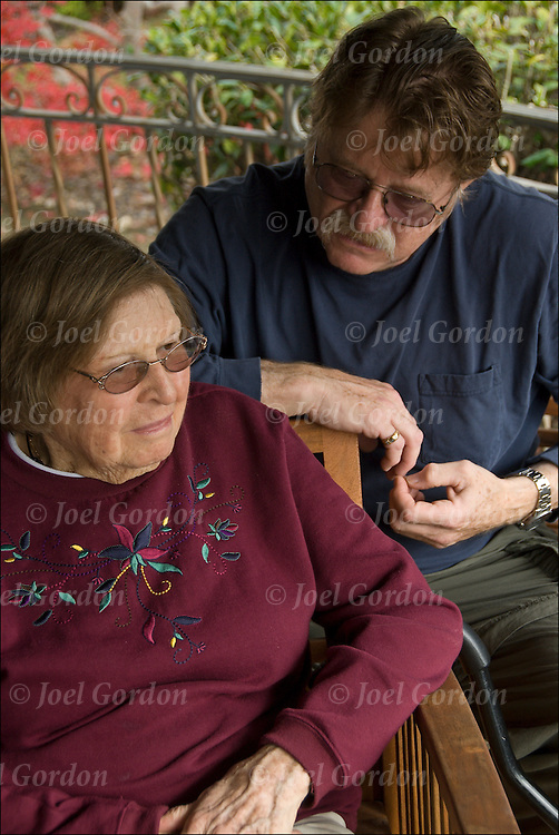 """Portrait of mother and son, he is both a baby boomer and a member of the """"Club Sandwich"""" generation.  The son is in his 60s has returned home to care for his 90 year old mother. A growing number, some 20 million people in the United States are caught up in what's  called the """"Sandwich Geneation"""", also known as the """"SandGEN"""".  Adults responsible for the care and support of both their children and elderly family members."""