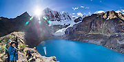 Hikers admire turquoise Solteracocha lake (4120 m) under glaciers of Nevado Jirishanca (Icy Beak of the Hummingbird, 6126 m or 20,098 feet). Day 9 of 9 days trekking around the Cordillera Huayhuash in the Andes Mountains, near Llamac, Peru, South America. This panorama was stitched from 6 overlapping photos.