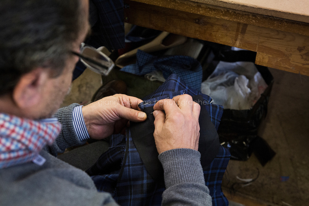 ARZANO, ITALY - 16 January 2014:  A tailor works on a blazer at the Kiton factory in Arzano, Italy, on January 16th 2014.