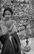 Woman smoking tobacco in waterpipe.<br />