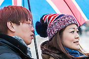 A new year's day parade passes through Piccadilly Circus on a wet and windy day.Many of the spectators are foreign and have just stocked up on Union Jack branded items.  London, UK 01 Jan 2014.