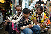 Azharuddin Ismail, 10, the child actor playing the role of 'young Salim', the brother of Jamal, protagonist of Slumdog Millionaire, the famous movie winner of 8 Oscar Academy Awards in December 2008, is sitting in front of his home along with his father, Mohammed Ismail, 45, (left) and mother, Shammi Bi, 36, (right) in the slum where they still live next to the train station of Bandra (East), Mumbai, India. Various promises were made to lift the two young actors (Azharuddin Ismail and Rubina Ali) from poverty and slum-life but as of the end of May 2009 anything is yet to happen. Rubina's house was recently demolished with no notice as it lay on land owned by the Maharashtra train authorities and she is now permanently living with her uncle's family in a home a stone-throw away in the same slum. Azharuddin's home too was demolished in the past two weeks, as it happens every year in his case, because the concrete walls were preventing local authorities to clear a drain passing right behind it. As usual, his father is looking into restoring the walls as soon as the work on the drain has been completed.