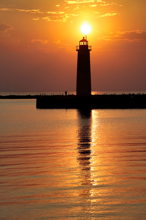 The setting sun silhouettes Muskegon Lighthouse on Lake Michigan.