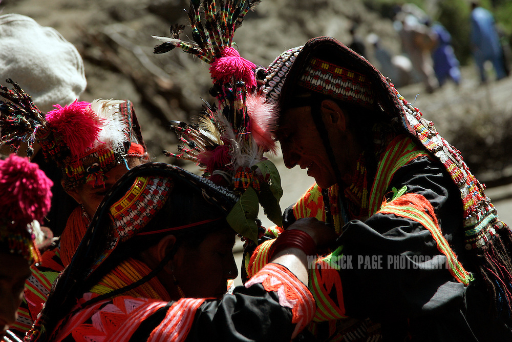 "KALASHA VALLEYS, PAKISTAN - MAY 15: Kalash women greet each other by kissing hands and cheeks during the ""Joshi"" (spring) festival in the village of Anish May 15, 2008 in the Kalasha Valleys, northwestern Pakistan. The Joshi Festival is a celebration of dance, music and prayer to welcome the coming of warmer season and the new life and crops it brings. The shrinking Kalash community of 4000, who claim to be descendants of Alexander the Great and worship several gods, are considered by many Pakistanis to be unclean, lazy and heretics. They often face ridicule and persecution for their polytheistic religion and fear the spread of hard-line Islamism bordering their communities. (Photo by Warrick Page)"