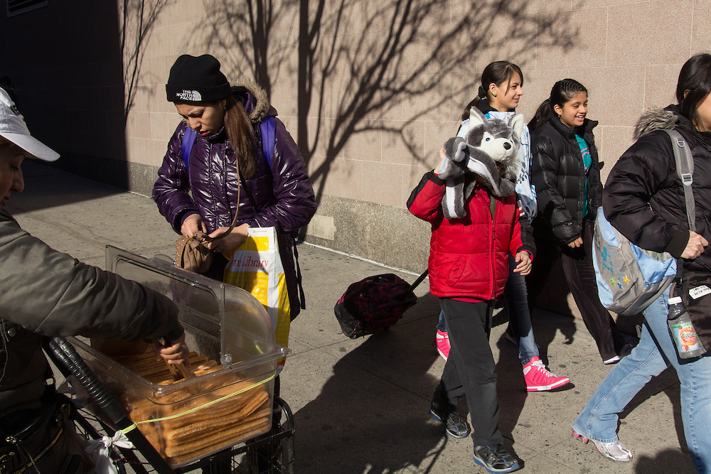 A street vendor sells churros after the bell rings at Renaissance Charter School, where the enrollment is one  of the most diverse among New York City charter schools.