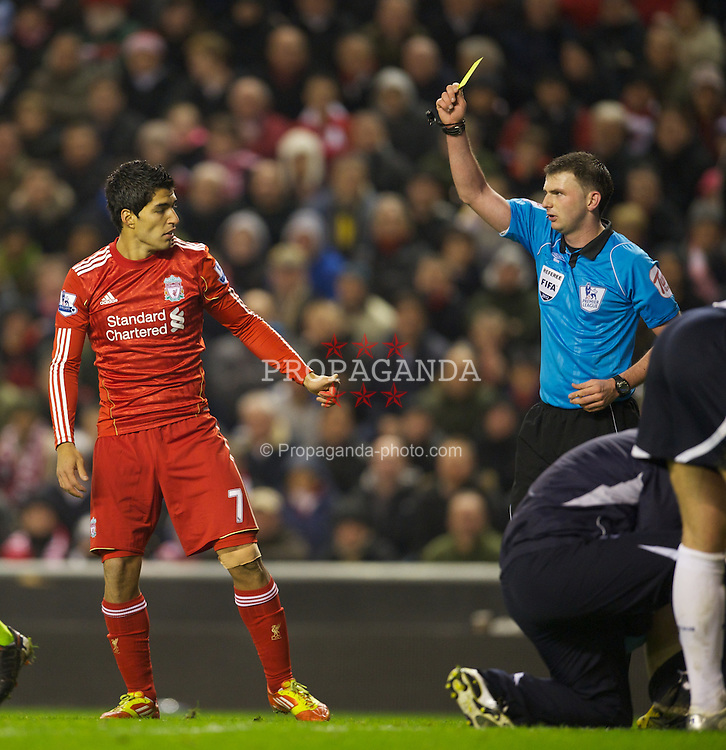 LIVERPOOL, ENGLAND - Monday, February 6, 2012: Liverpool's Luis Alberto Suarez Diaz is shown the yellow card by referee Michael Oliver against Tottenham Hotspur during the Premiership match at Anfield. (Pic by David Rawcliffe/Propaganda)