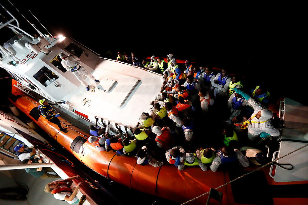 Rescued migrants stand in a Italian Coast Guard vessel after transferring from the Migrant Offshore Aid Station (MOAS) ship MV Phoenix between Libya and the Italian island of Lampedusa, August 3, 2015.  Some 118 migrants were rescued by the MOAS ship MV Phoenix from a rubber dinghy around 20 miles (32 kilometres) off the coast of Libya on Monday morning. The Phoenix, manned by personnel from international non-governmental organisations Medecins san Frontiere (MSF) and MOAS, is the first privately funded vessel to operate in the Mediterranean.<br /> REUTERS/Darrin Zammit Lupi <br /> MALTA OUT. NO COMMERCIAL OR EDITORIAL SALES IN MALTA