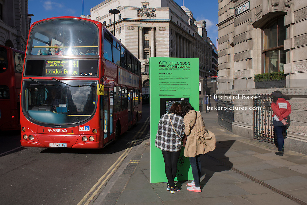 As a red London double-decker bus of the Arriva company passes-by, two pedestrians inspect a map for the City of London.
