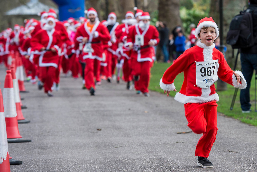A young runner takes an early lead at the start - The London Santa Run 2015 in Battersea Park - 2,000 Santa's take part in an annual 'Red & White' bearded 'charge' around Battersea Park in a 6k festive charity fun run. The runners are of all ages and abilities and many run at a very slow pace but enjoy the event and the cause. The Santa Run is organised to raise funds for Disability Snowsport UK, a national charity helping people with disabilities to access the thrill of snowsports. The charity ensures that children and adults, with a range of disabilities (including cerebral palsy, Down's syndrome,  visual impairment and autism), can access programs across the UK to enable them to make friends, improve their confidence and have fun through a sport which they would otherwise be excluded from.
