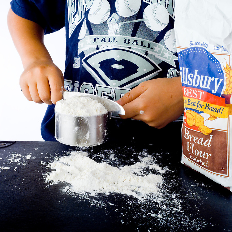 Boy using a measuring cup to measure a quantity of flour.