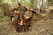 "Left, Mee Moua Vang, with family infront of their make shift home, near Vang Vieng, Laos, June 28, 2006.  Her message  to the world, ""My husband and two older daughters were killed by the communist while foraging for food.  My daughter Blee was attacked by the communist where her guts were sticking out and I was unable to help her so she died.  I miss her very much.  I am desperately suffering here with no help.  I ask you to come in and save us.  Bring us food.""...**EXCLUSIVE, no tabloids without permission**  .These pictures are from a group of Hmong people who report an attack against them April 6, 2006 by Lao and Vietnamese military forces.  26 people perished, 5 were injured, and 5 babies died shortly after because their dead mothers could not breast-feed them.  Only one adult male was killed, the other 25 victims were women and children (17 children).  The Lao Spokesman for the Ministry of Foreign Affairs says this is a fabrication, an investigation has been completed, and there was no attack.   The Hmong group says no officials have interviewed witnesses or visited the crime scene, a point the Lao Spokesman did not deny.  ..The Hmong people in these pictures have been hiding in the remote mountains of Laos for more than 30 years, afraid to come out.  At least 12,000 are estimated to exist. Since 1975, under the communists, thousands of reports evidence the Hmong have suffered frequent persecution, torture, mass executions, imprisonment, and possible chemical weapons attacks.  Reports of these atrocities continue to this day.  The Lao Government generally denies the jungle people exist or that any of this is happening.  The Hmong group leader, Blia Shoua Her, says they want peace, and are just civilians defending their families hoping to surrender to the UN.."