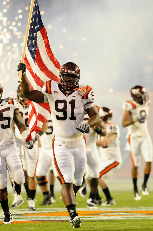 January 1, 2009: John Graves of the Virginia Tech Hokies carries the American flag onto the field before the NCAA football game between the Virginia Tech Hokies and the Cincinnati Bearcats in the Orange Bowl Classic. The Hokies defeated the Bearcats 20-7.