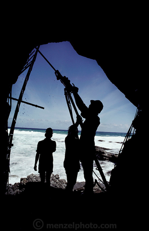 Fossil mining. Research team members at Dinosaur Cove pin steel reinforcing mesh to the wall of their mine with long expansion bolts driven in by a jackhammer. Dinosaur Cove is situated near Cape Otway in southern Australia.  Dinosaur Cove is the world's first mine developed specifically for paleontology, normally the scientists rely on commercial mining to make the excavations. The site is of particular interest as the fossils found date from about 100 million years ago, when Australia was much closer to the South Pole than today [1989].