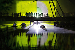 © Licensed to London News Pictures . 22/07/2013 . Suffolk , UK . People on Writers' Bridge over a lake in Henham Park silhouetted against a large projected light show . Revellers enjoy the final night of the Latitude Festival . The Latitude music and culture festival in Henham Park , Southwold . Photo credit : Joel Goodman/LNP