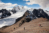 Trekkers descend from the summit of Pico Austria (17,348 ft / 5300 m) in Bolivia's Cordillera Real during typical winter weather with Mt. Condoriri (18,525' / 5648 m) dominating the skyline in the background.