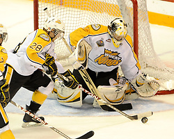 Darren Bestland of the Brandon Wheat Kings shovels the puck away from goalie Jacob de Serres in Game 6 of the 2010 MasterCard Memorial Cup in Brandon, MB on Wednesday May 19, 2010. Photo by Aaron Bell/CHL Images