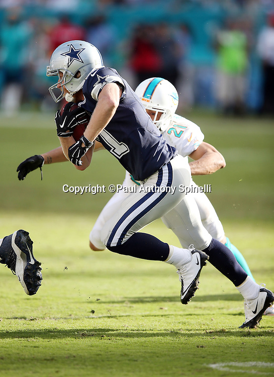 Dallas Cowboys wide receiver Cole Beasley (11) catches a key pass for a first down that helps burn the clock in the fourth quarter while being chased by Miami Dolphins cornerback Brent Grimes (21) during the 2015 week 11 regular season NFL football game against the Miami Dolphins on Sunday, Nov. 22, 2015 in Miami Gardens, Fla. The Cowboys won the game 24-14. (©Paul Anthony Spinelli)