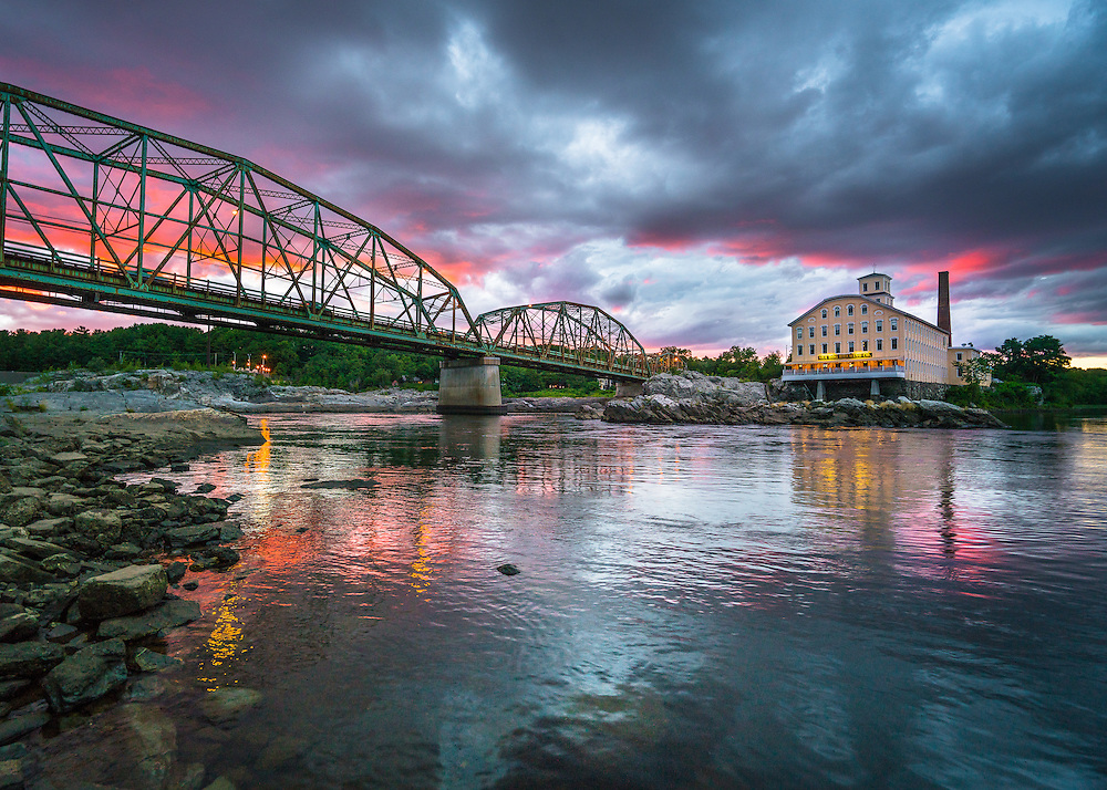 A fiery summer sunset erupts behind the Green Bridge and Bowdoin Mill as seen from across the Androscoggin River in Brunswick.