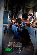 A floor sweeper clears the filth on the Himsagar Express 6318 on 8th July 2009.. .6318 / Himsagar Express, India's longest single train journey, spanning 3720 kms, going from the mountains (Hima) to the seas (Sagar), from Jammu and Kashmir state of the Indian Himalayas to Kanyakumari, which is the southern most tip of India...Photo by Suzanne Lee / for The National