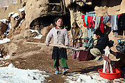 Hamidah, 6, (Centre) is playing with a shovel while other members of the family are washing clothes or arranging morning duties, in front the cave they live since seven years, during a cold winter morning in Bamyan, central Afghanistan, an area mostly populated by Hazaras. A historically persecuted minority (15%) due to more lenient Islamic faith and characteristic 'Eastern' lineaments, Hazaras constitute the 70% of Bamyan's population.