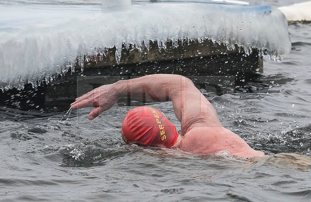 © Licensed to London News Pictures. 03/03/2018. London, UK. Members of the Serpentine Swimming Club brave freezing overnight temperatures as they enjoy an early morning race at sunrise in the Serpentine in Hyde Park, London. Large parts of the UK are recovering from a week of sub zero temperatures and heavy snowfall, following two severe cold fronts. Photo credit: Ben Cawthra/LNP
