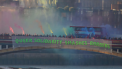 "© Licensed to London News Pictures. 20/01/2017. London, UK.  As part of the 'Bridges not Walls' campaign of national demonstrations against Donald Trump, members of the LGBT community suspended a banner from Vauxhall Bridge in London reading ""QUEER SOLIDARITY SMASHES BORDERS"". Donald Trump will attend his inauguration ceremony in Washington later today. Photo credit: Ben Cawthra/LNP"