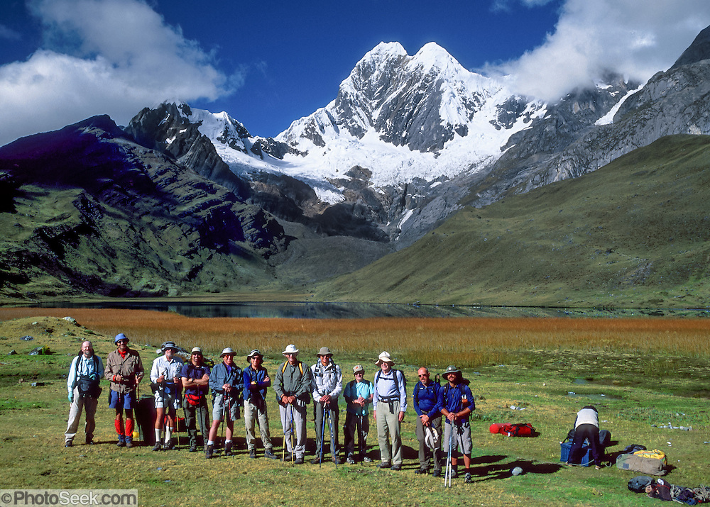 "Trekkers line up at Lake Mitococha (13,900 feet) beneath glaciers of Mount Jirishanca (""Icy Beak of the Hummingbird,"" north face, 6126 m or 20,098 feet elevation), third highest peak in the Cordillera Huayhuash, tenth highest in Peru. Andes Mountains, South America."