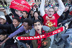 © Licensed to London News Pictures . 13/05/2013 . Manchester , UK . Fans at the Manchester United trophy parade outside Manchester Town Hall this evening (Monday 13th May) . The team are celebrating their 20th league title win and commemorating the retirement of manager , Sir Alex Ferguson , by carrying the trophy on an opened top bus through the city . Photo credit : Joel Goodman/LNP