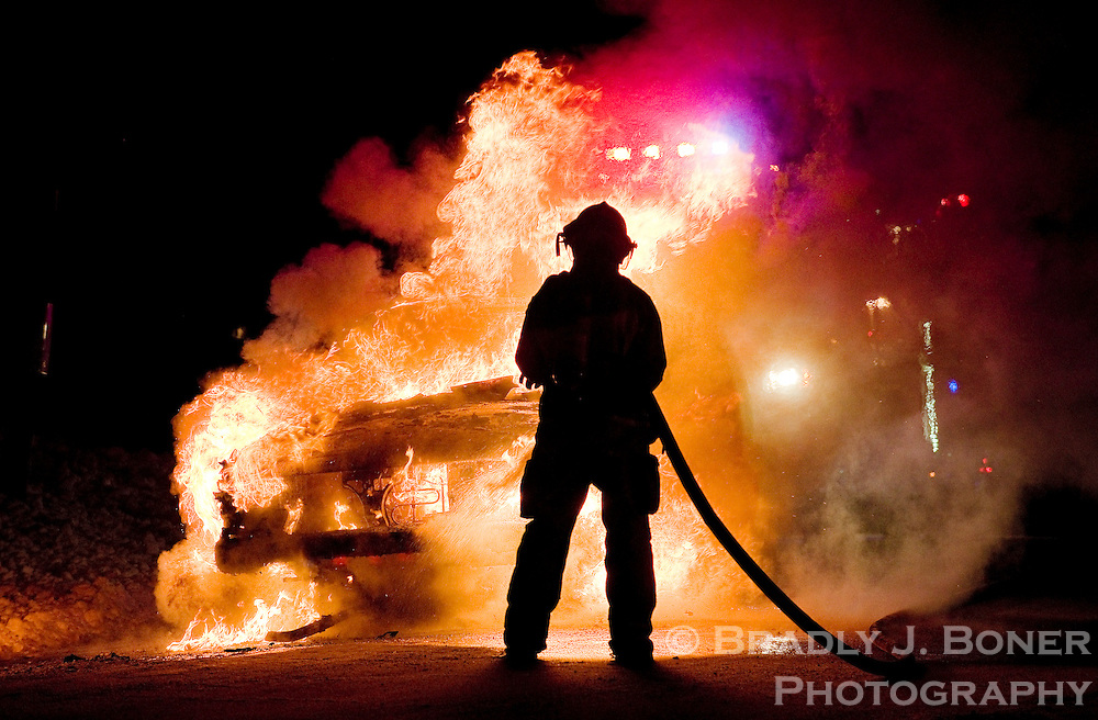 A firefighter from Jackson Hole Fire/EMS sprays water on a car that caught fire Monday evening at the summit of Teton Pass. The driver and passenger of the car escaped the vehicle uninjured.