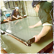 Artisans remove small impurities as they tilt a frame to create an even sheet of washi paper at Iwano Heizaburo Seijijo in Echizen, Fukui Prefecture, Japan on 21 Feb. 2013. Photographer: Robert Gilhooly  .