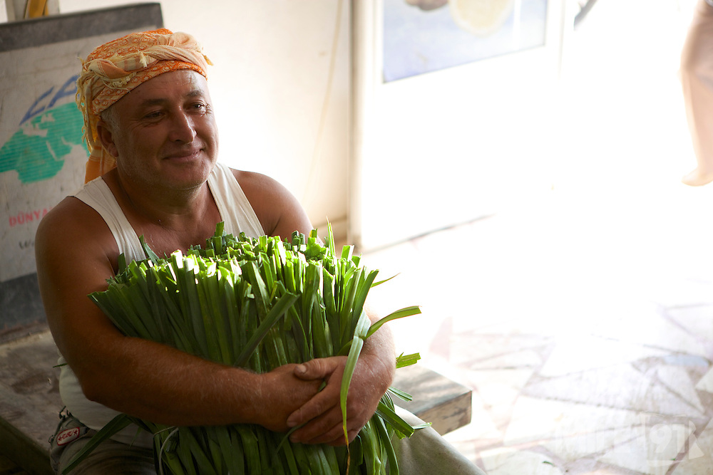 A farmer holding some leeks at the wholesalers shop.